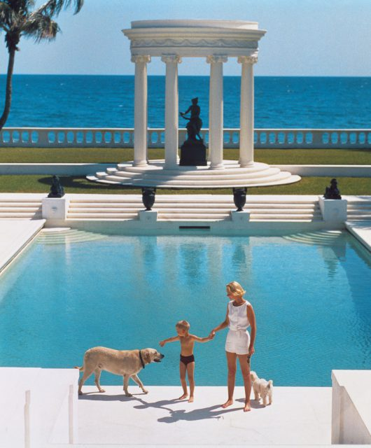 American writer C.Z. Guest (Mrs F.C. Winston Guest, 1920 - 2003) and her son Alexander Michael Douglas Dudley Guest in front of their Grecian temple pool on the ocean-front estate, Villa Artemis, Palm Beach. Original Publication: A Wonderful Time - Slim Aarons  (Photo by Slim Aarons/Getty Images)
