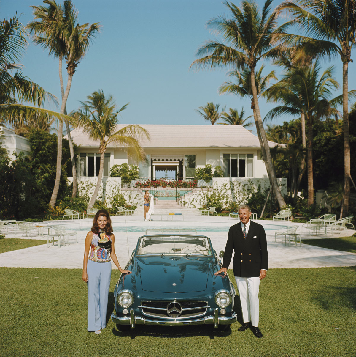 May 1970: Alvin and Lilly Fuller outside their new home in Palm Beach, Florida, pose with their fashionable European sports car, the Mercedes 190SL. (Photo by Slim Aarons/Getty Images)